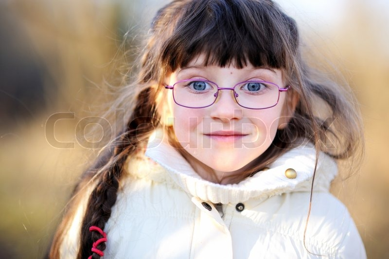 A Portrait Of Little Girl With Long Hair Wearing Glasses