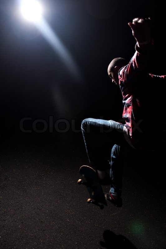 A skateboarder performs tricks under dramatic low key lighting with bright lens flare Shallow depth of field | Stock Photo | Colourbox & A skateboarder performs tricks under dramatic low key lighting ... azcodes.com