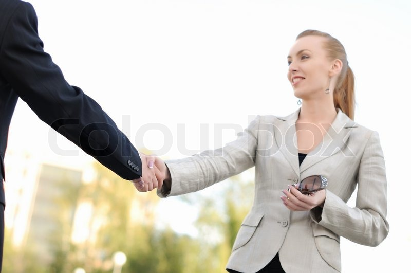 Business men and women shaking hands on a light background ...