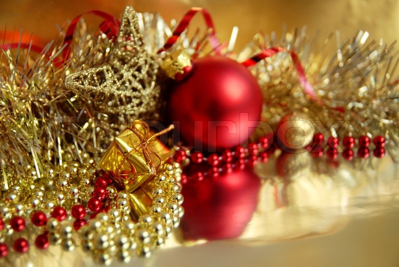 still life of red and gold christmas ornaments in the foreground a small gift stock photo colourbox