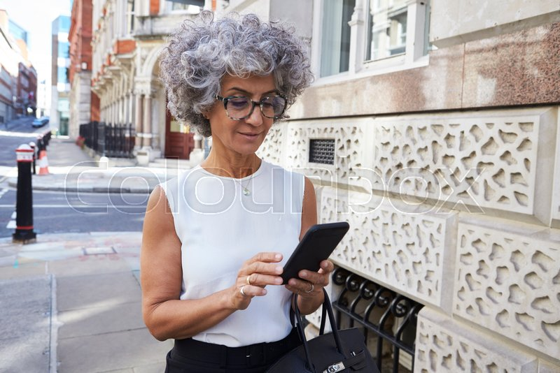 Middle aged woman using smartphone in city street, stock photo