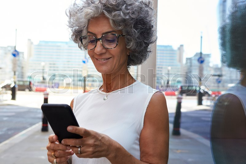 Middle aged woman using smartphone in city street, close up, stock photo