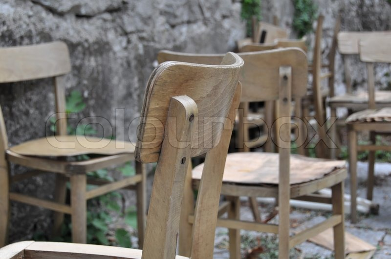 Set Of Old School Chairs Being Lined Up In Front Of A Rough Wall In The  Outside | Stock Photo | Colourbox