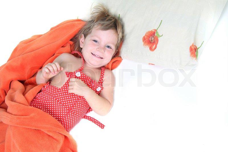 l chelnde kind im bett isoliert auf wei em stockfoto colourbox. Black Bedroom Furniture Sets. Home Design Ideas