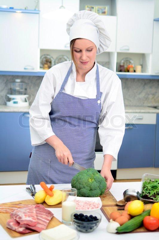 attractive chief cook preparing food cuts cauliflower stock photo
