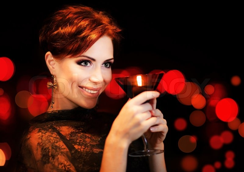 Stock image of 'Beautiful female partying, celebrating holiday, portrait of a woman holding martini glass, girl over black background with red blur bokeh lights, luxury nightlife'