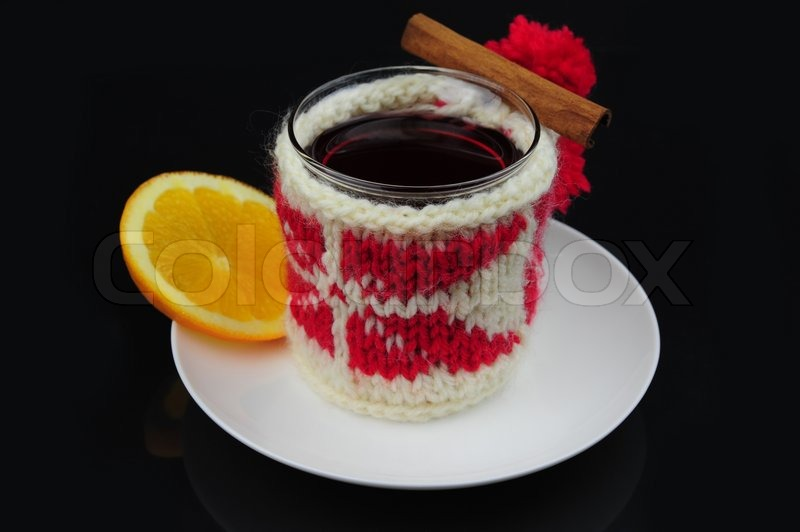Stock image of 'Cup of hot drink in winter knitted cover with red and white ornaments, cinnamon stick, a slice of orange on a black background'