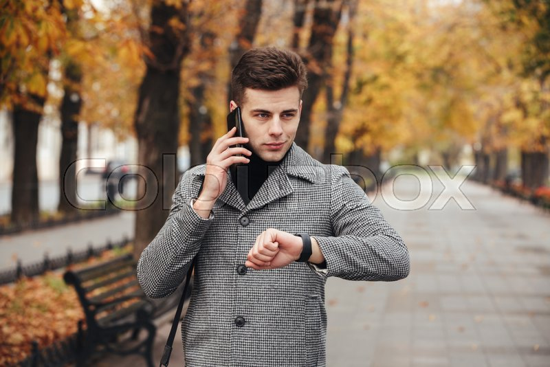 Picture of elegant man checking time with watch on hand, and speaking on mobile phone during his walk in park, stock photo
