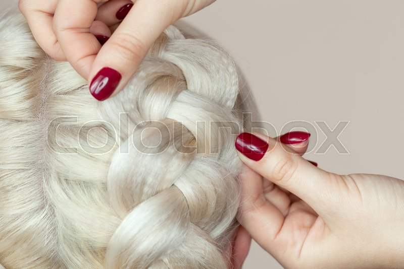 Beautiful Girl With Blonde Hair Hairdresser Weaves A Braid Close Up