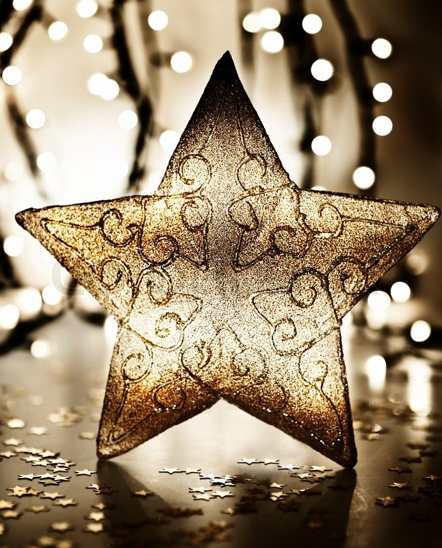 Star christmas tree ornament golden decoration over blur