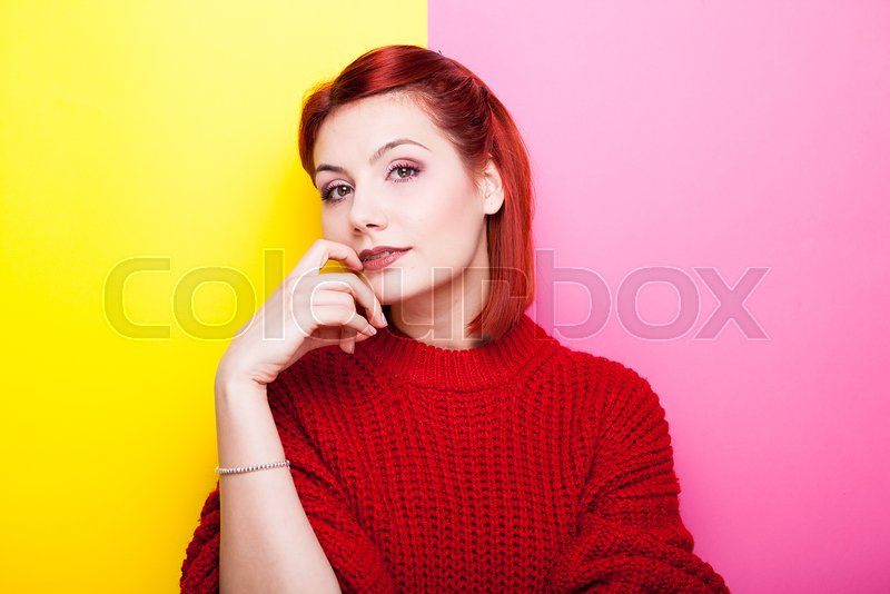 Stock image of 'Sexy redhead woman looking at the camera on two colored background in yellow and pink'