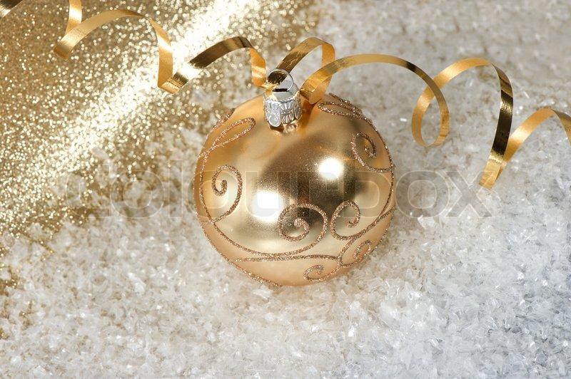 goldene weihnachtskugel mit streamer und schnee dekoration ber gl nzendem hintergrund. Black Bedroom Furniture Sets. Home Design Ideas