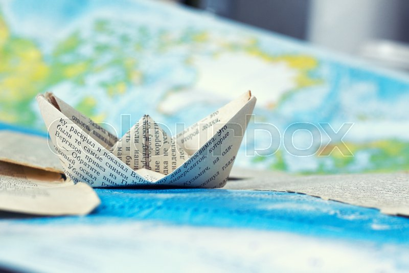 A paper ship goes on a journey . travel of a paper ship, stock photo