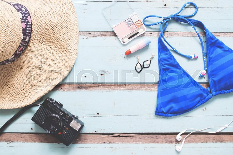 Overhead view of Woman\'s essentials summer vacation concept on vintage blue wooden background, stock photo
