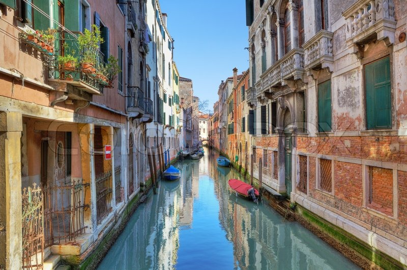 Venice Italy Architecture small narrow canal with boats among ancient multicolored houses in