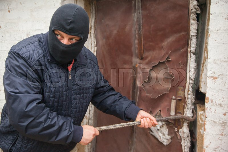 Stock image of 'A thief with a crowbar near house'