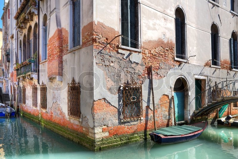Ancient Brick Building On Small Canal With Boats And Bridge In Venice Italy Stock Photo