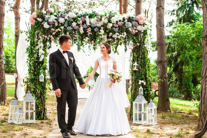 Adorable beauty wedding couple under flower arch. Wedding holiday ...
