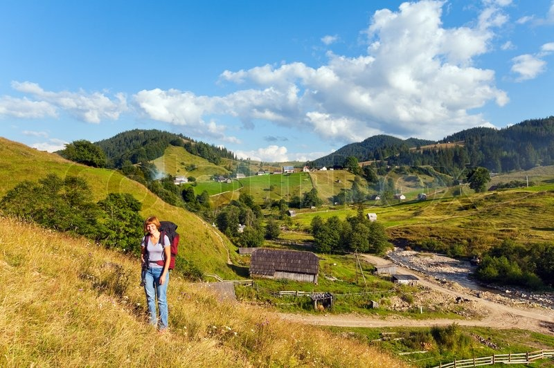 Summer mountain village landscape and woman with tripod, stock photo