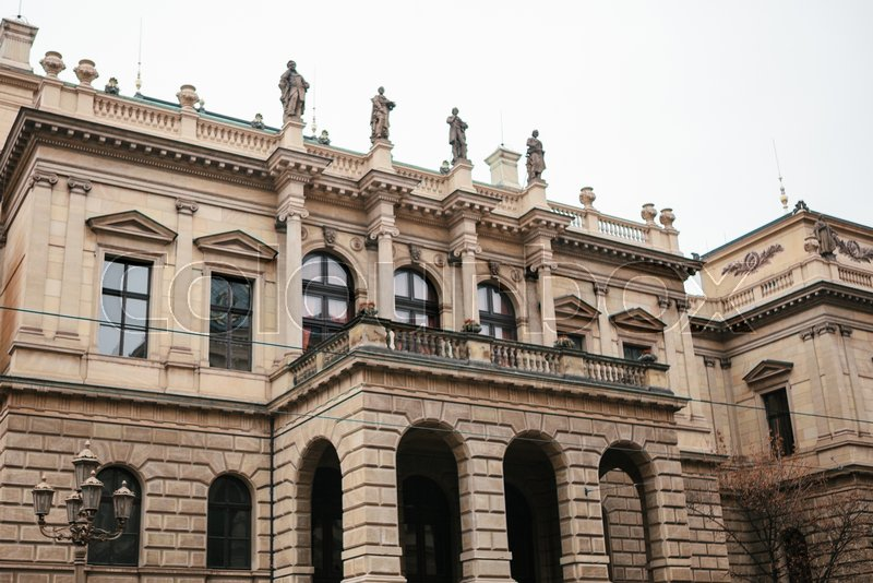 Beautiful historical building in Prague with balcony, columns and sculptures standing at the top. Czech architecture, stock photo