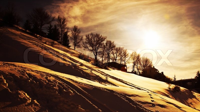 Winter sunset, beautiful mountains landscape, village covered with snow, cold weather wintertime seasonal nature, dramatic sky with warm sun light, stock photo