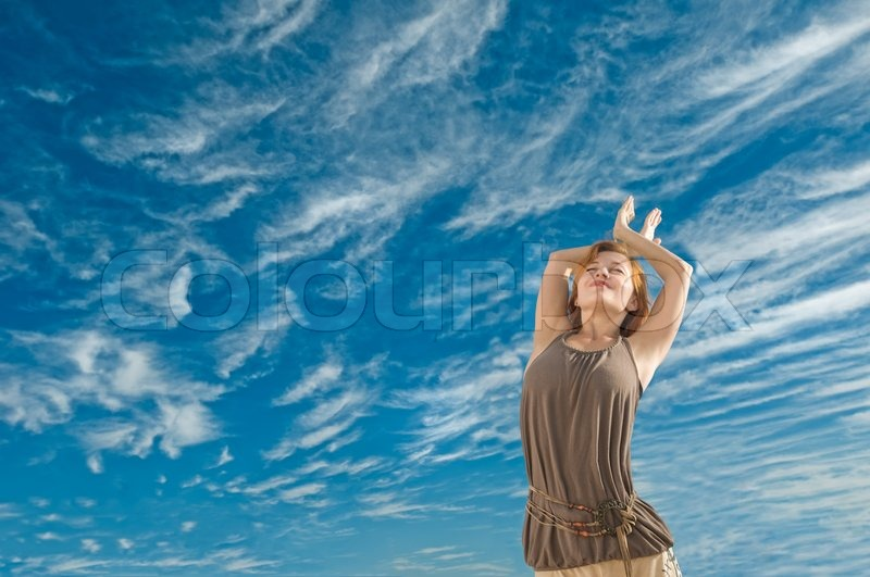 Beautiful Young Dancer Performing Yoga Dance Outdoors With Blue Sky And Clouds In The Background