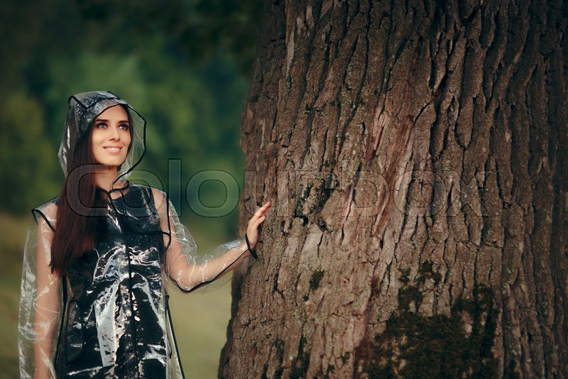 Trendy Woman in Clear Transparent Raincoat in Summer Rain, stock photo