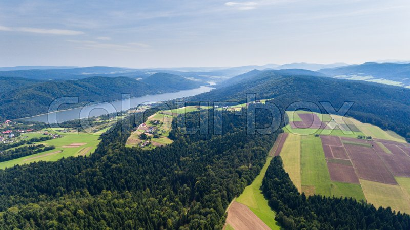 Landscape with lake, fields, forest and farmland. Drone view from above, stock photo