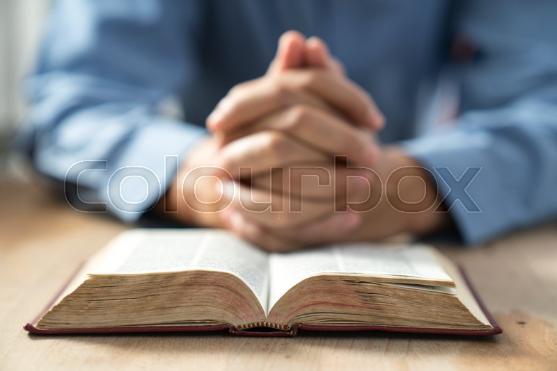 An unknown man holding a Bible in her ...