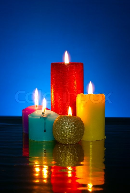 Five Burning Colourful Candles Against Blue Background