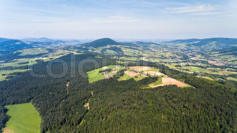 Forest, village and green fields summer landscape from above - drone view, stock photo