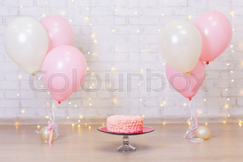 Stock image of 'birthday celebration background - cake over brick wall with lights and colorful balloons'