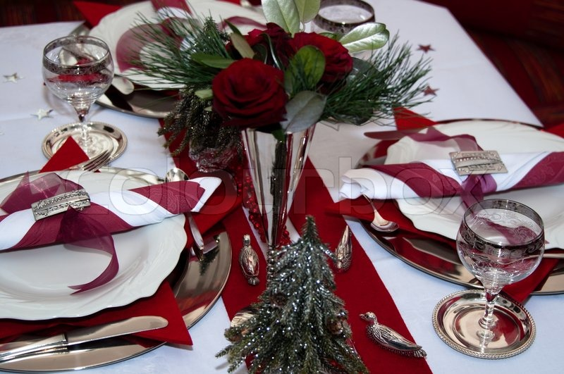 Christmas table with red decoration, napkins, roses ...