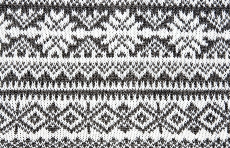 Gray background with a knitted pattern to form snowflakes Stock Photo Col...