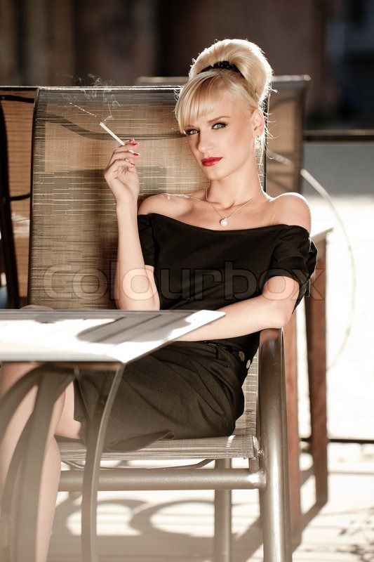 Stock image of '50s styled woman sitting in a street cafe and smoking cigarette'