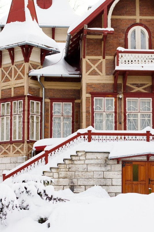 The front of a older home covered in deep snow, stock photo
