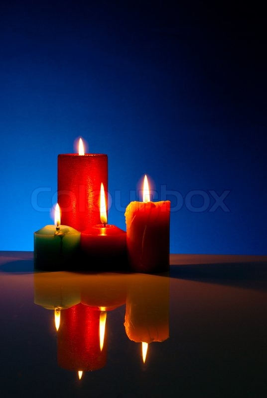 Four Burning Colorful Candles Against Black Background