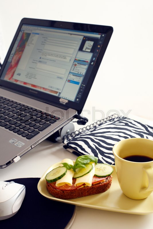 coffee mug and sandwich on table in front of laptop during