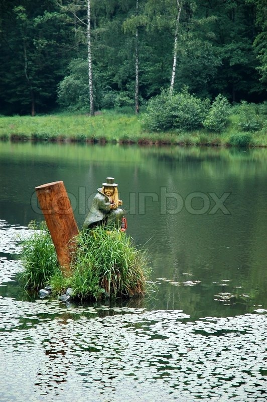 Stock image of 'Statue of water sprite sitting on the pond water'