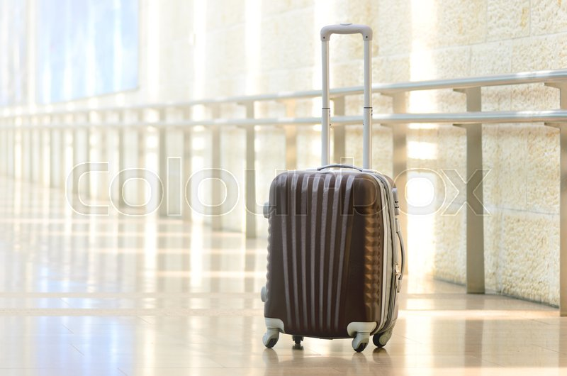 Packed travel suitcase, airport. Summer holiday and vacation concept. Traveler baggage, brown luggage in empty hall interior. Copy space, stock photo