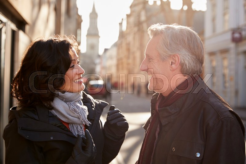 Middle Aged Couple Walking Through City In Fall Together, stock photo