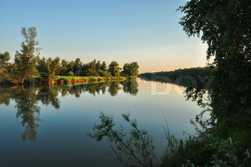 Tranquil nature scene. Water surface and green shores of the river Ob in soft evening sunset colors. Altai, Russia, stock photo