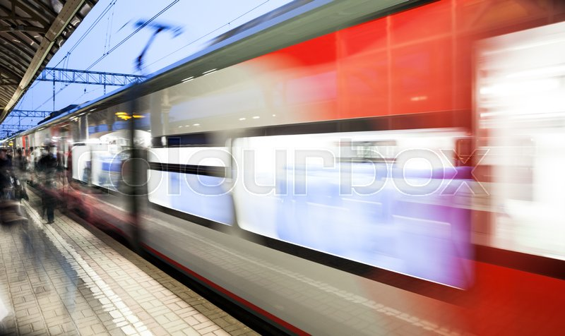 Motion blurred high speed moving passenger commuter railroad train at railway station or subway platform, stock photo