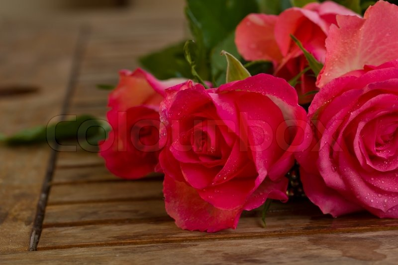 Bouquet of pink roses in water droplets on wooden table ...