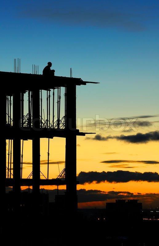 Lonely Construction Worker Sitting At Stock Photo