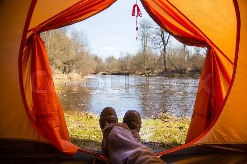 A person sitting in an orange tent, camp in the bank of the river in spring. Feet selfie of traveler. Relaxed, colorful look. Spring hiking, stock photo