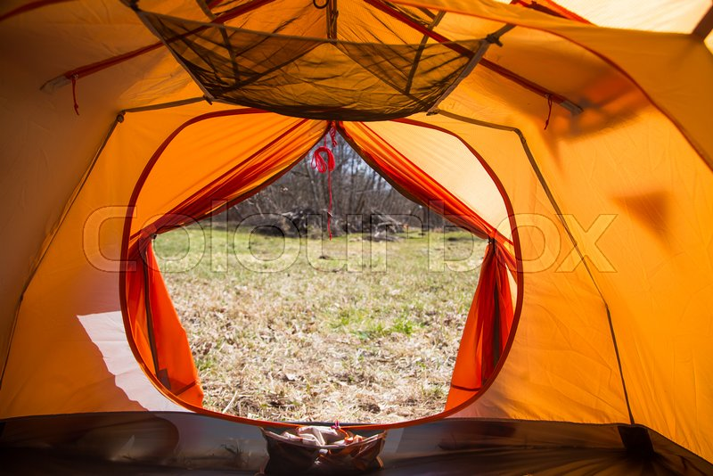 A look through the entrance of the tent. Orange camping tent in an early spring. Exit door, stock photo