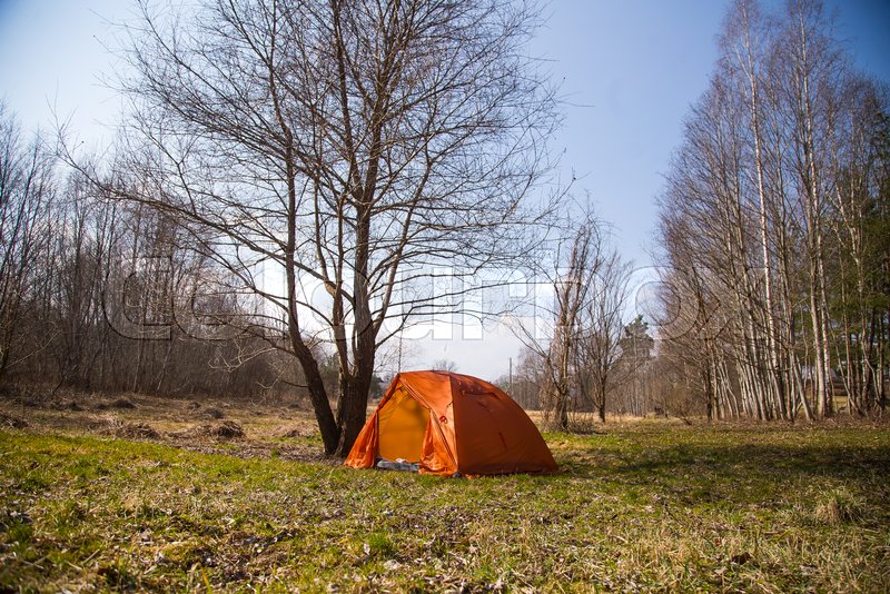 An orange tent built on the bank of the river. Hiking camp in the spring. Early spring scenery, stock photo