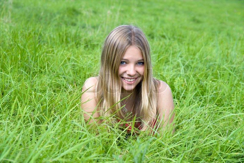 Beautiful girl lying on grass field | Stock Photo | Colourbox