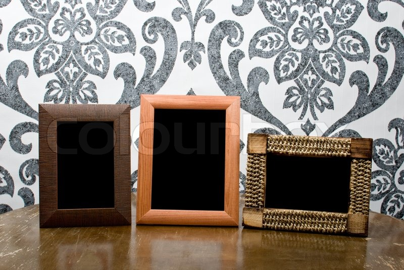 Three wooden photo frames on old table on vintage wallpaper ...